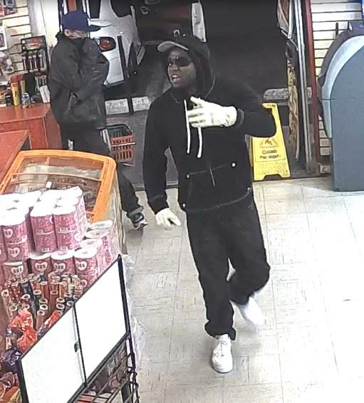Third Suspect Approaches Counter with Second Suspect in Background
