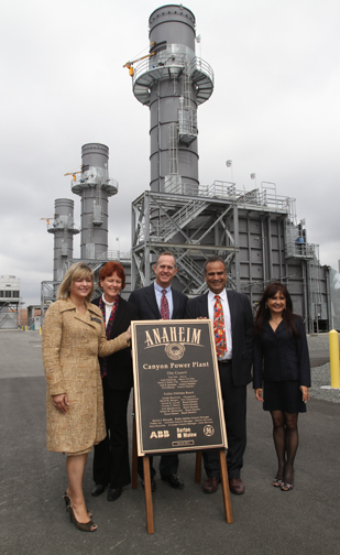 Men and women stand next to plaque in front of power plant