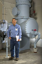Man standing next to water service equipment