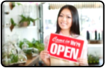 Women holding a red come in we're open sign
