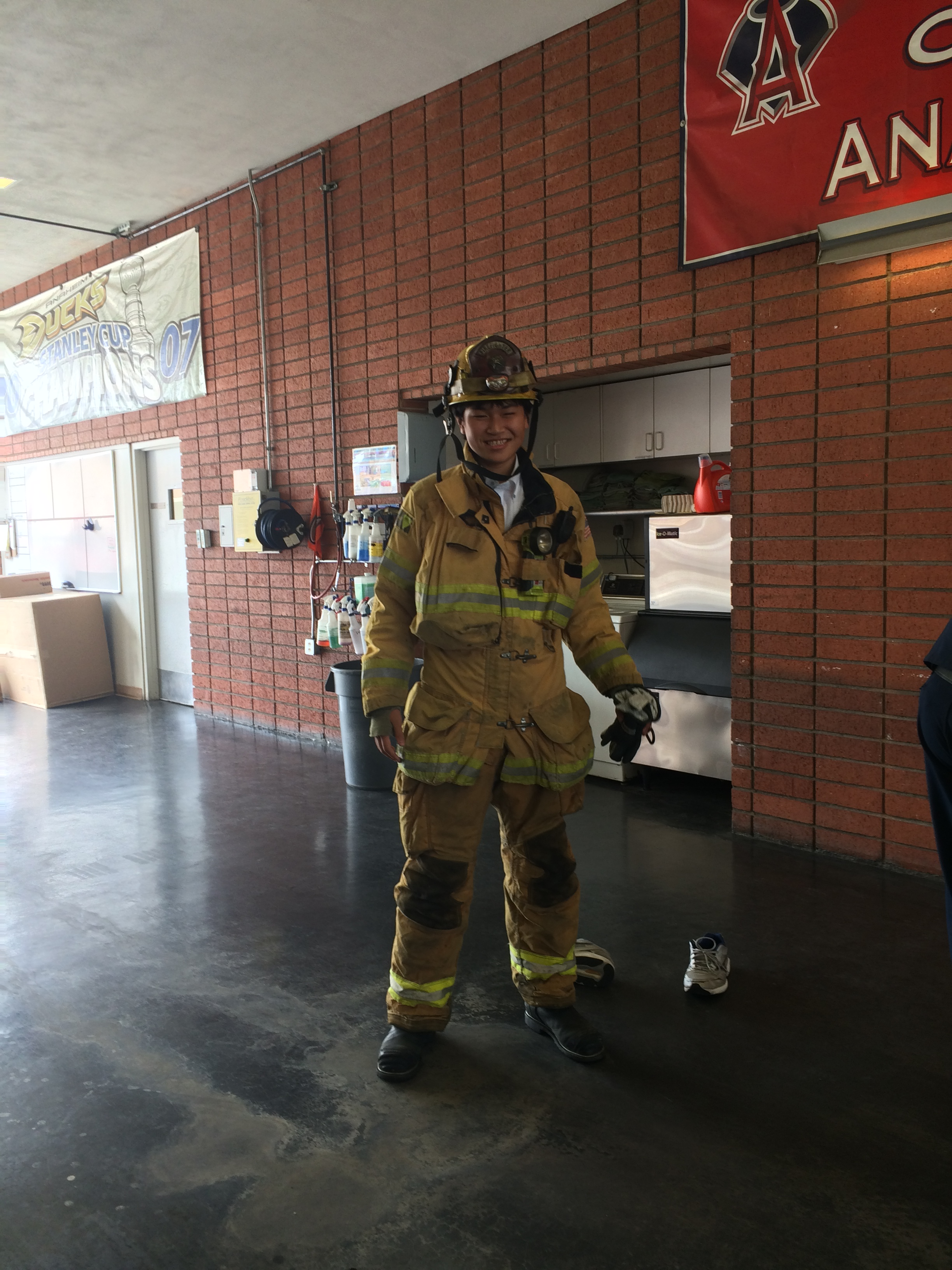 One student trying on firefighter jacket, pants, and helmet.