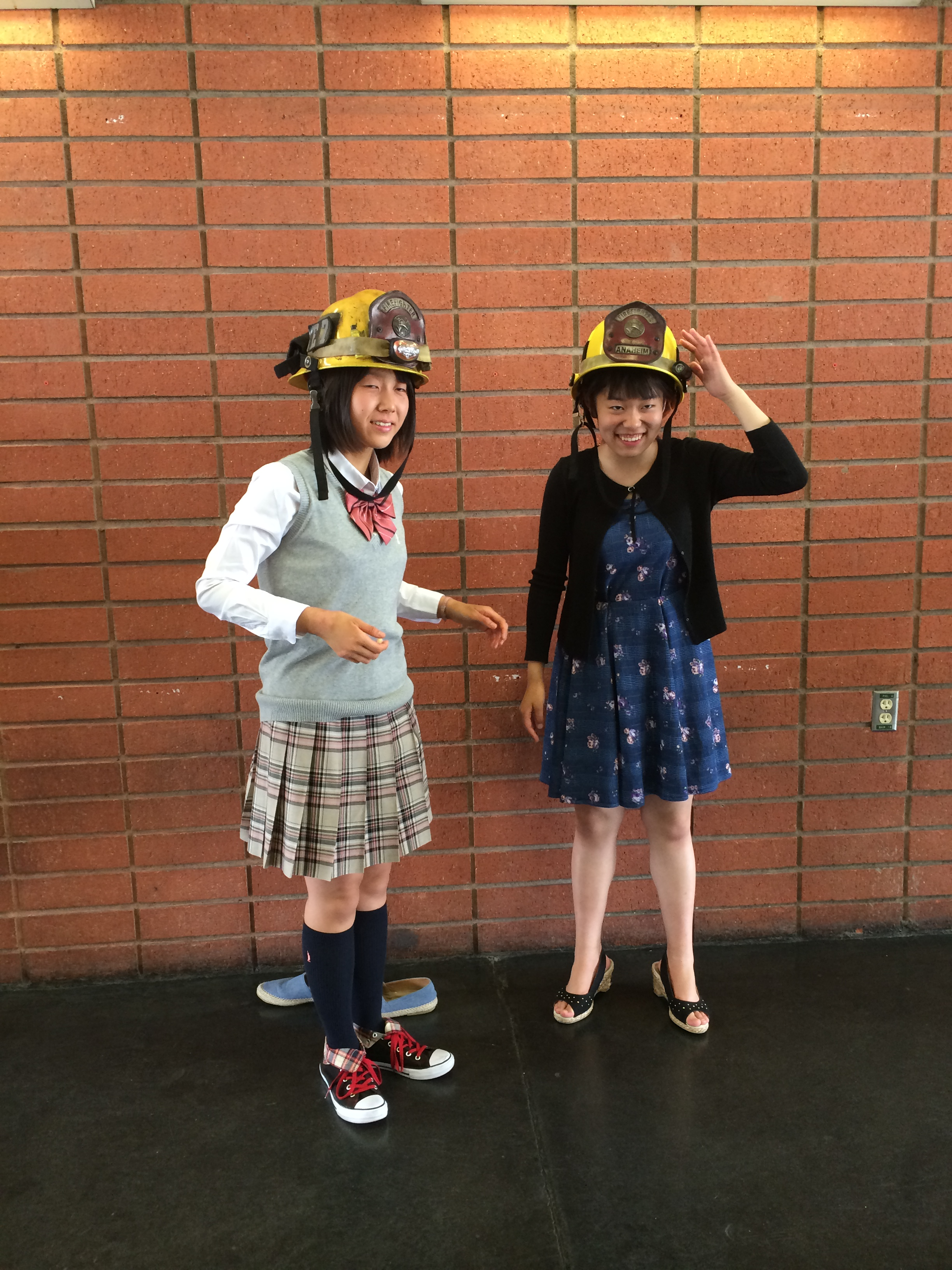 Two girls trying on firefighter helmets