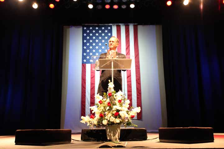 Mayor Tom Tait at the podium giving the 2012 State of the City Address with the American flag behind him