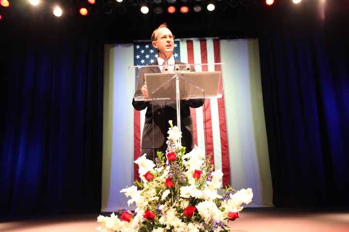 Mayor Tom Tait at the podium giving the 2012 State of the City Address with the American flag behind him and a flower arragement in front
