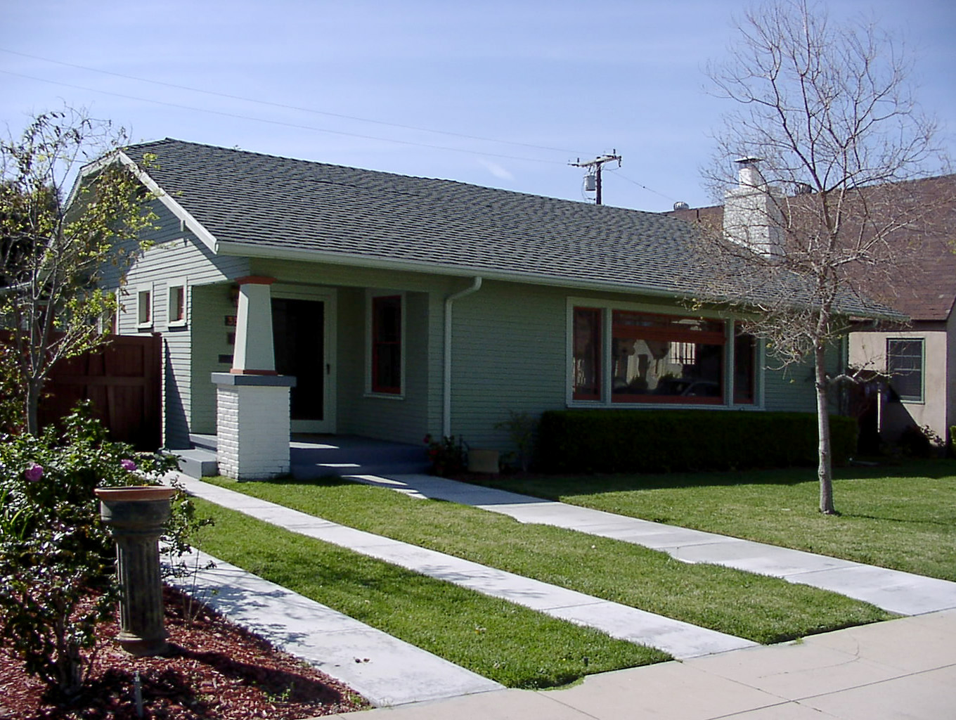 House with a walkway and a driveway that has grass growing in the middle of the driveway