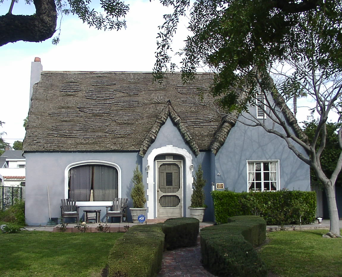 Blue house with tall pointed roof and hedges on both sides of the walkway