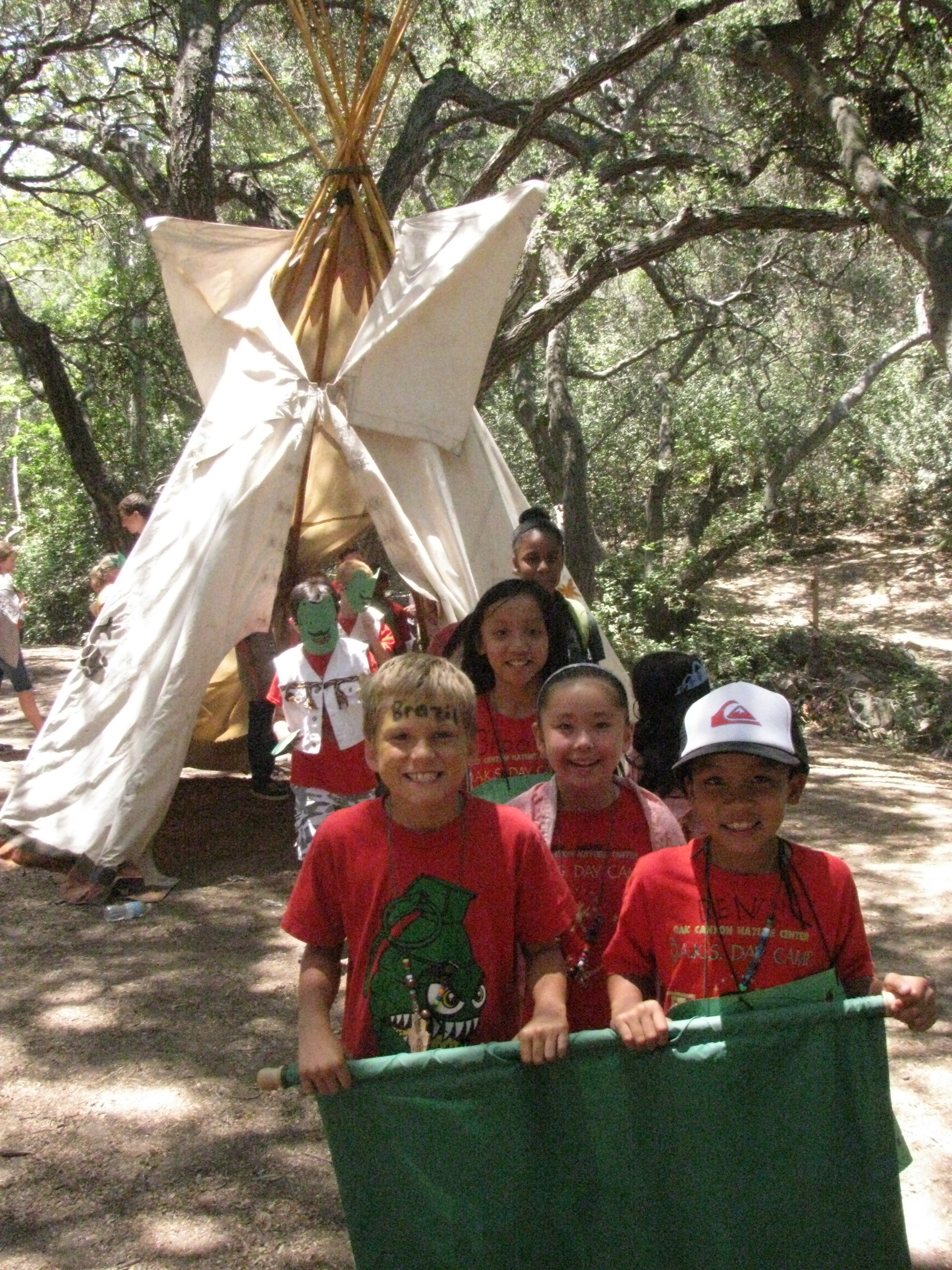 Kids hold a banner in front of a teepee