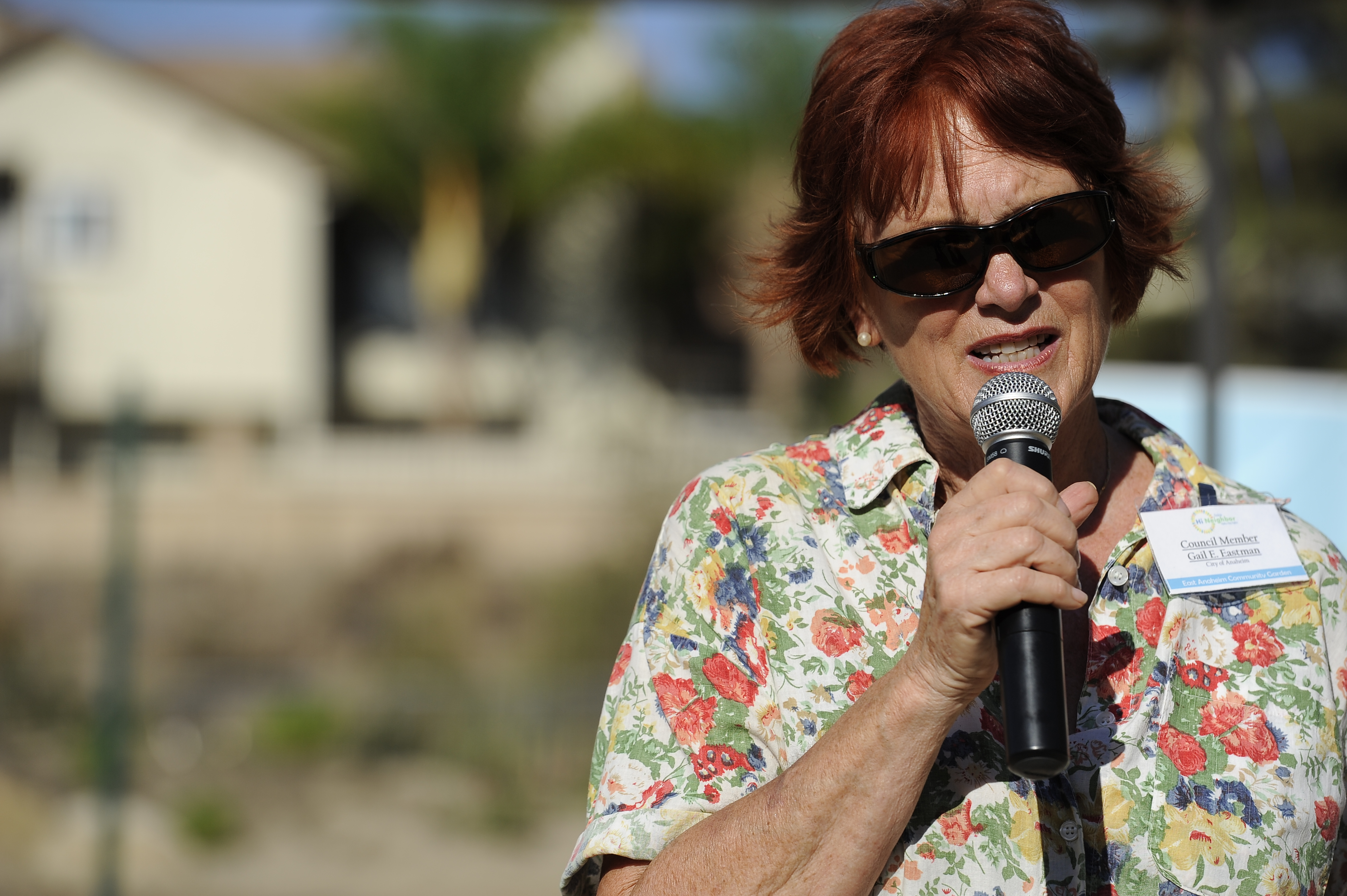 Woman wearing sunglasses talking into a microphone