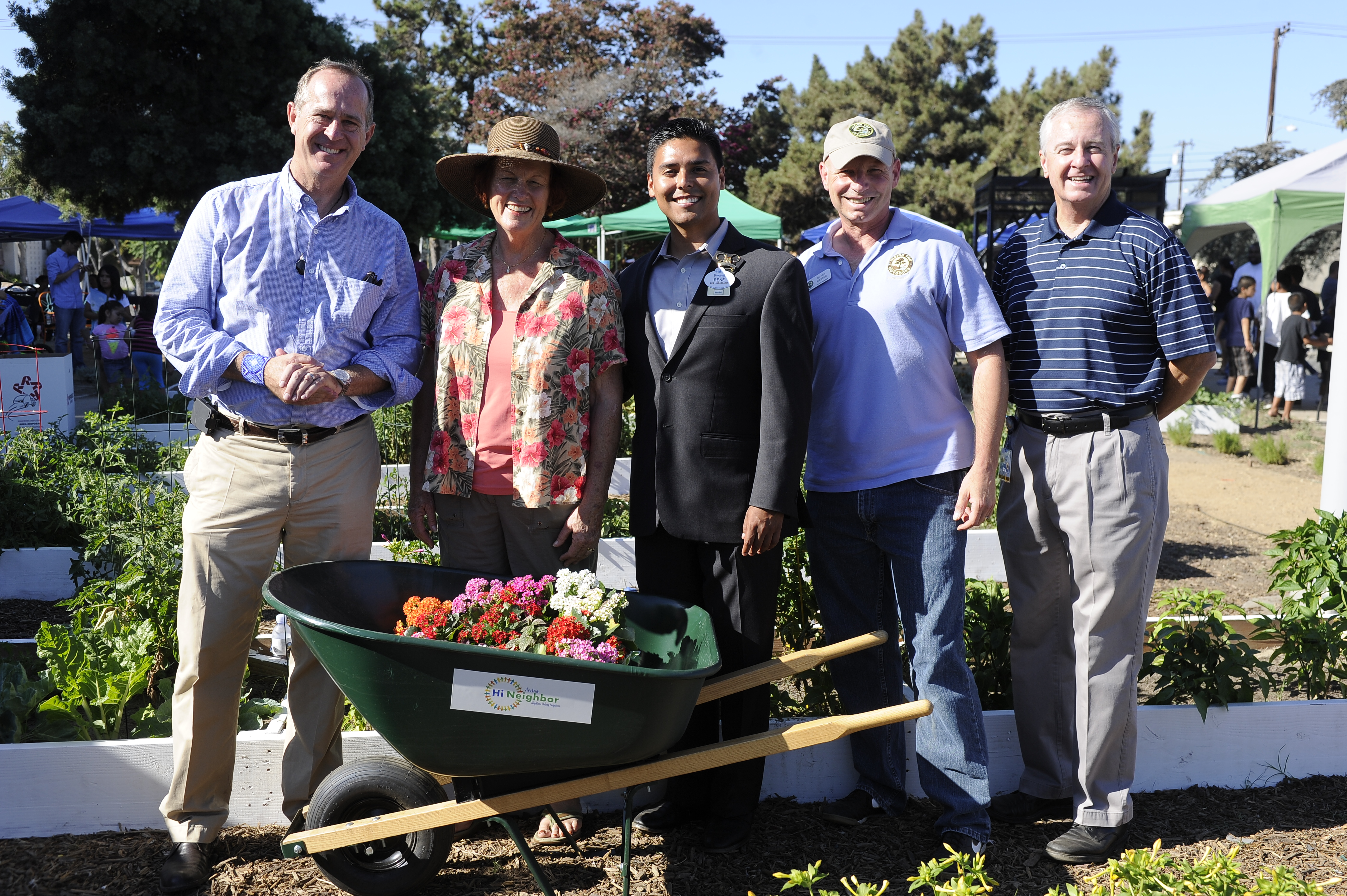 Group photo with a wheel barrel full of produce