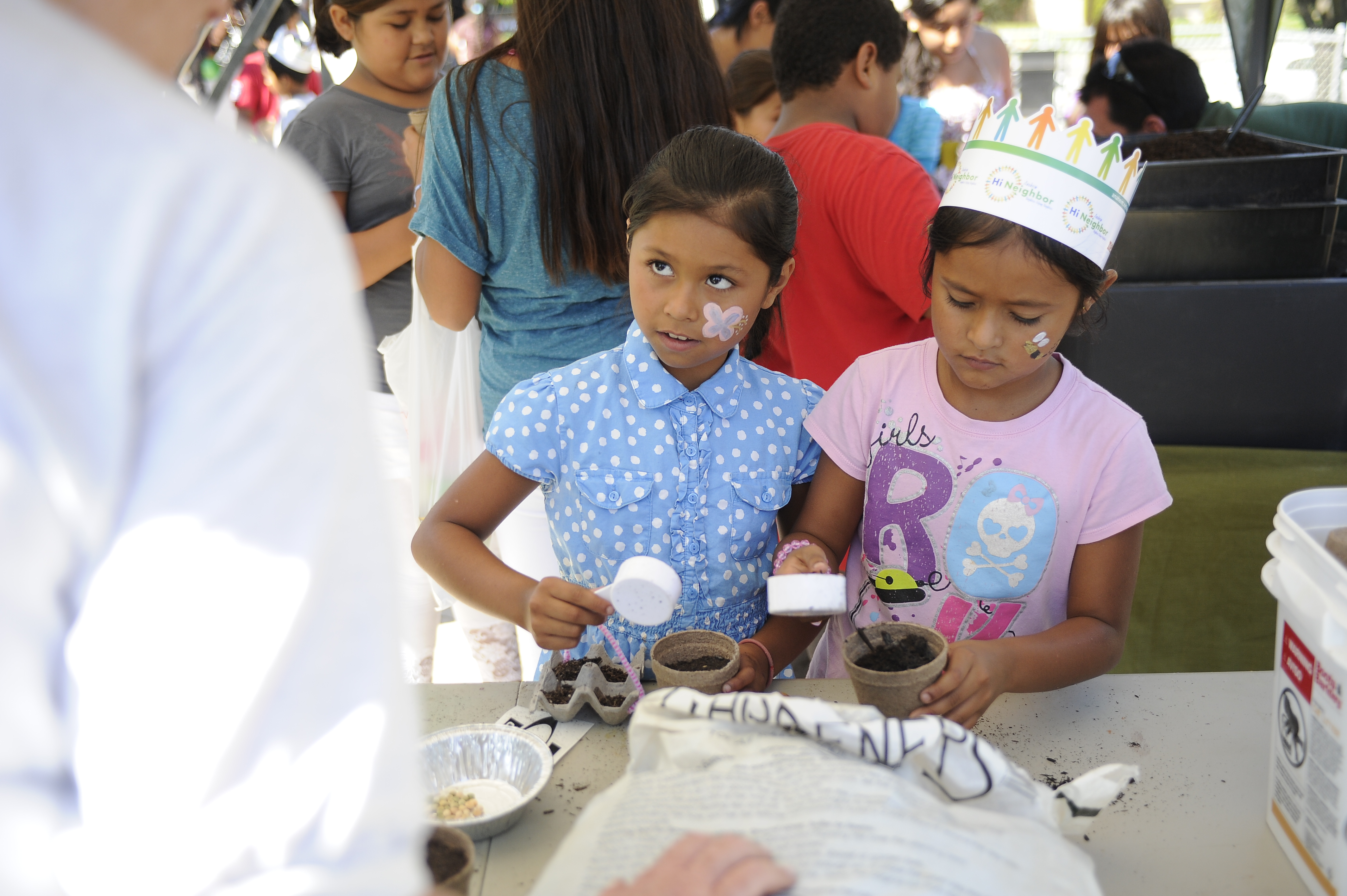 Two young girls with face paint planting their seedlings
