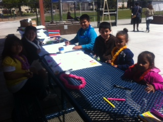 Group of people and children at a table working on a drawing for the garden plots