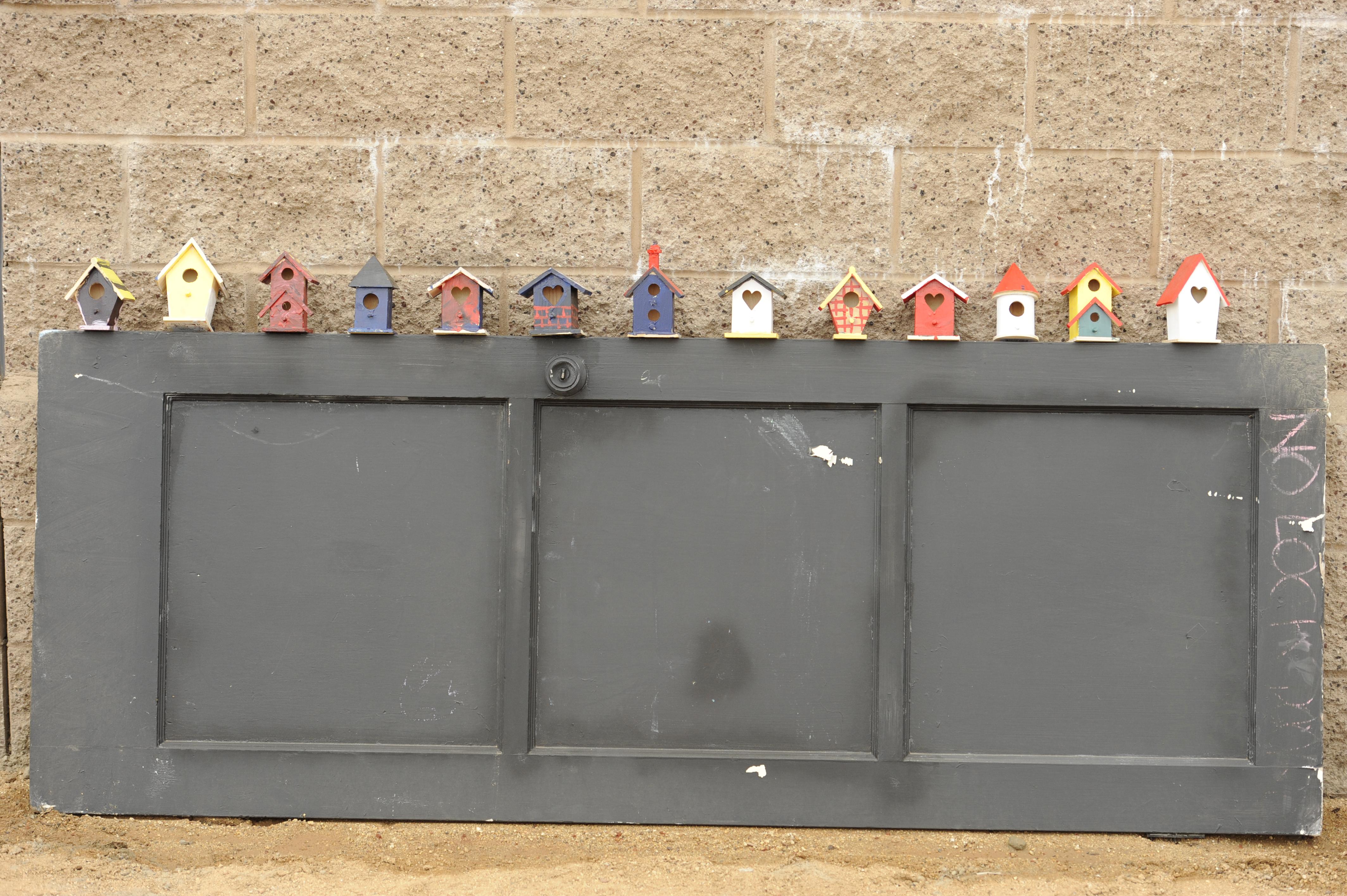 13 small bird houses on display