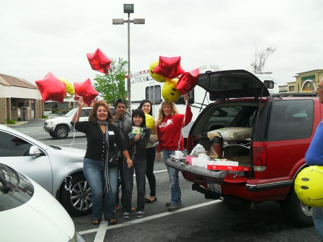 Group of people getting out of their car holding balloons