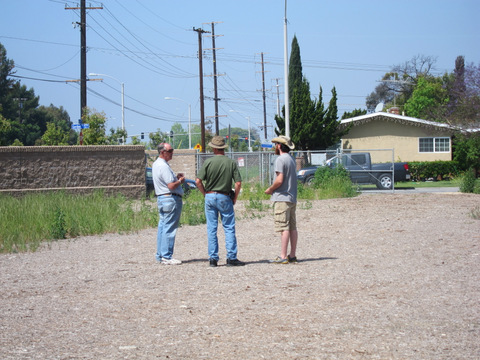 Three men standing in the the empty lot