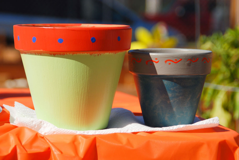 Two painted flower pots drying in the sun