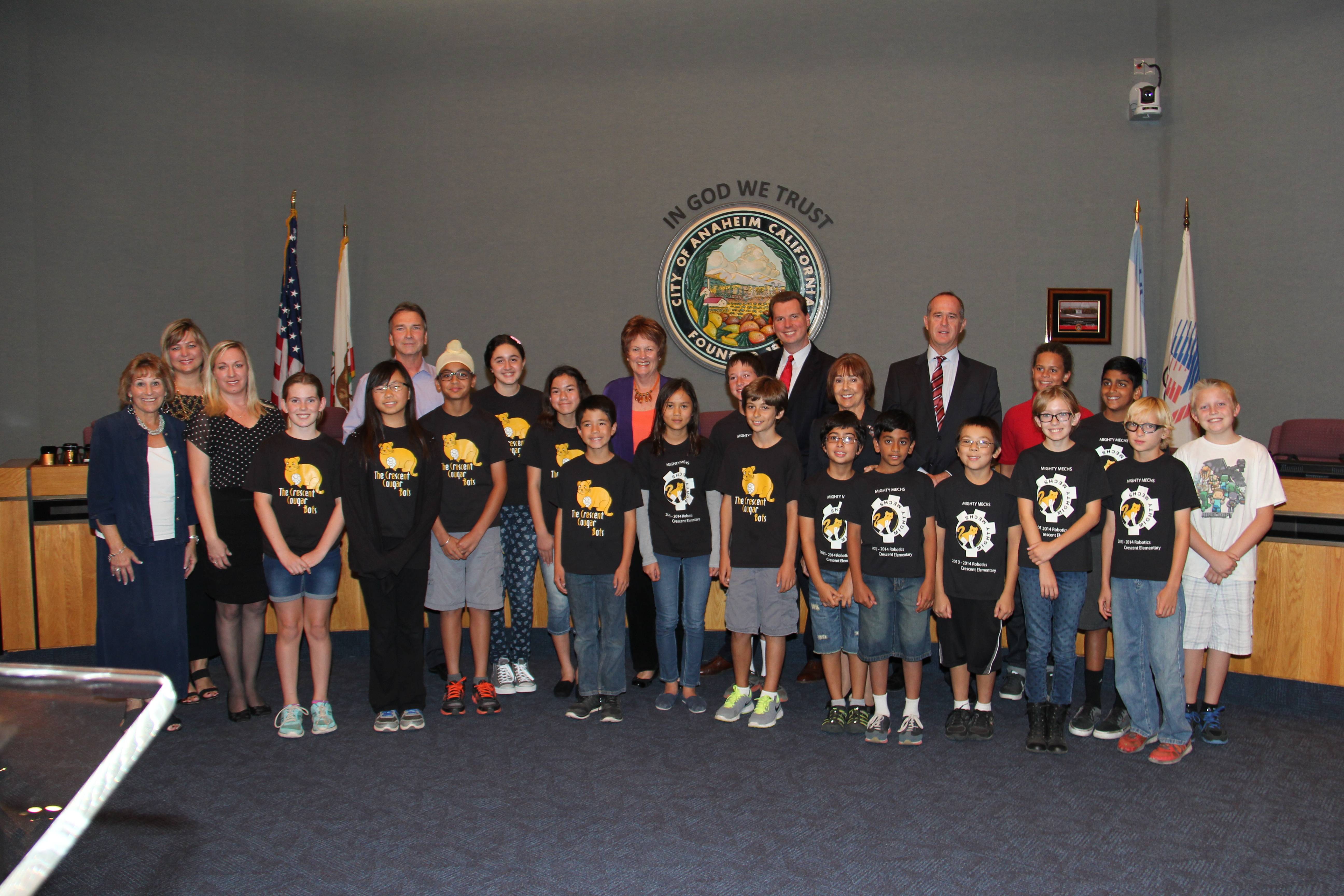 The students from Crescent Cougar Bots are taking a group photo with councilmembers