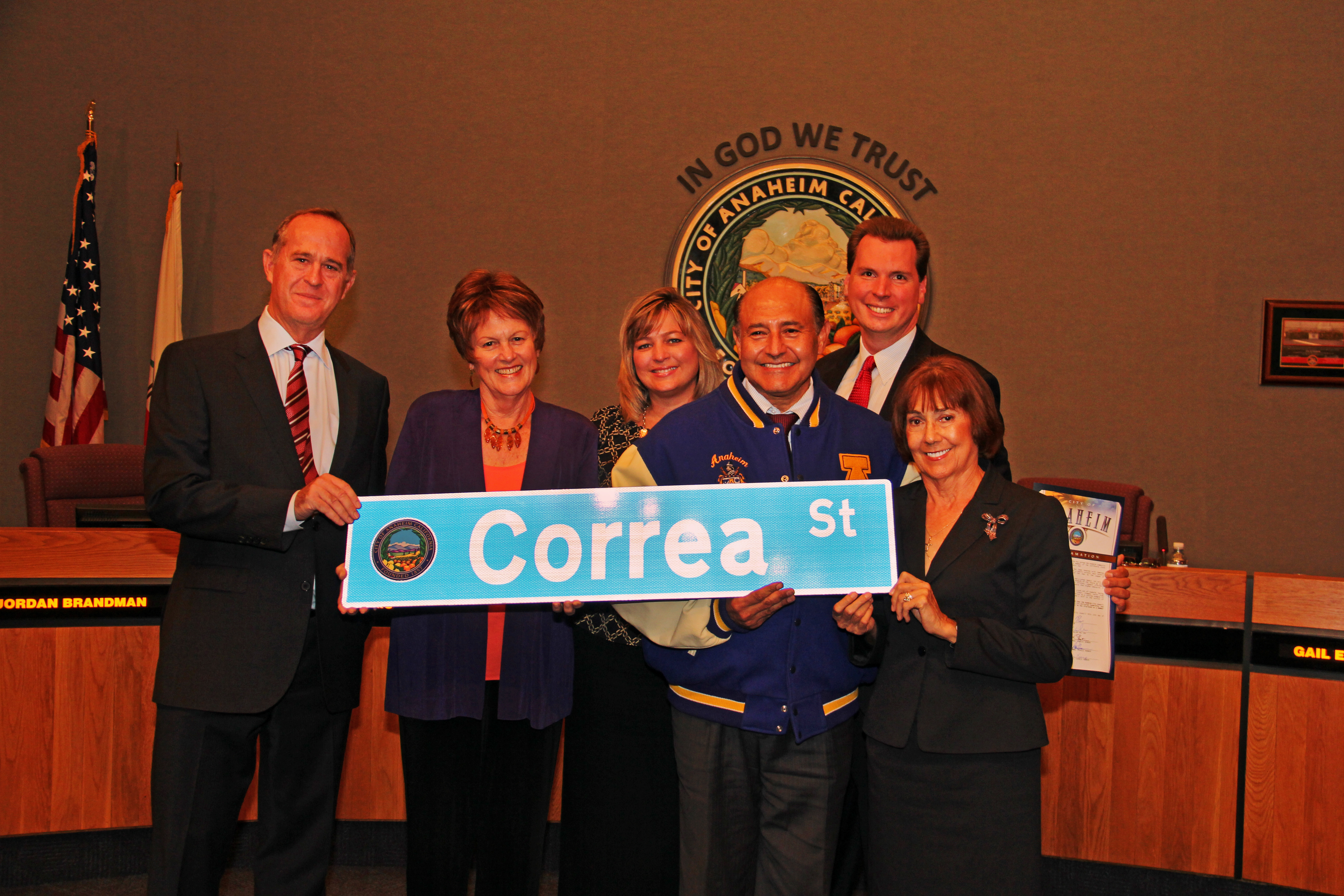 Group of people holding the Correa Street sign