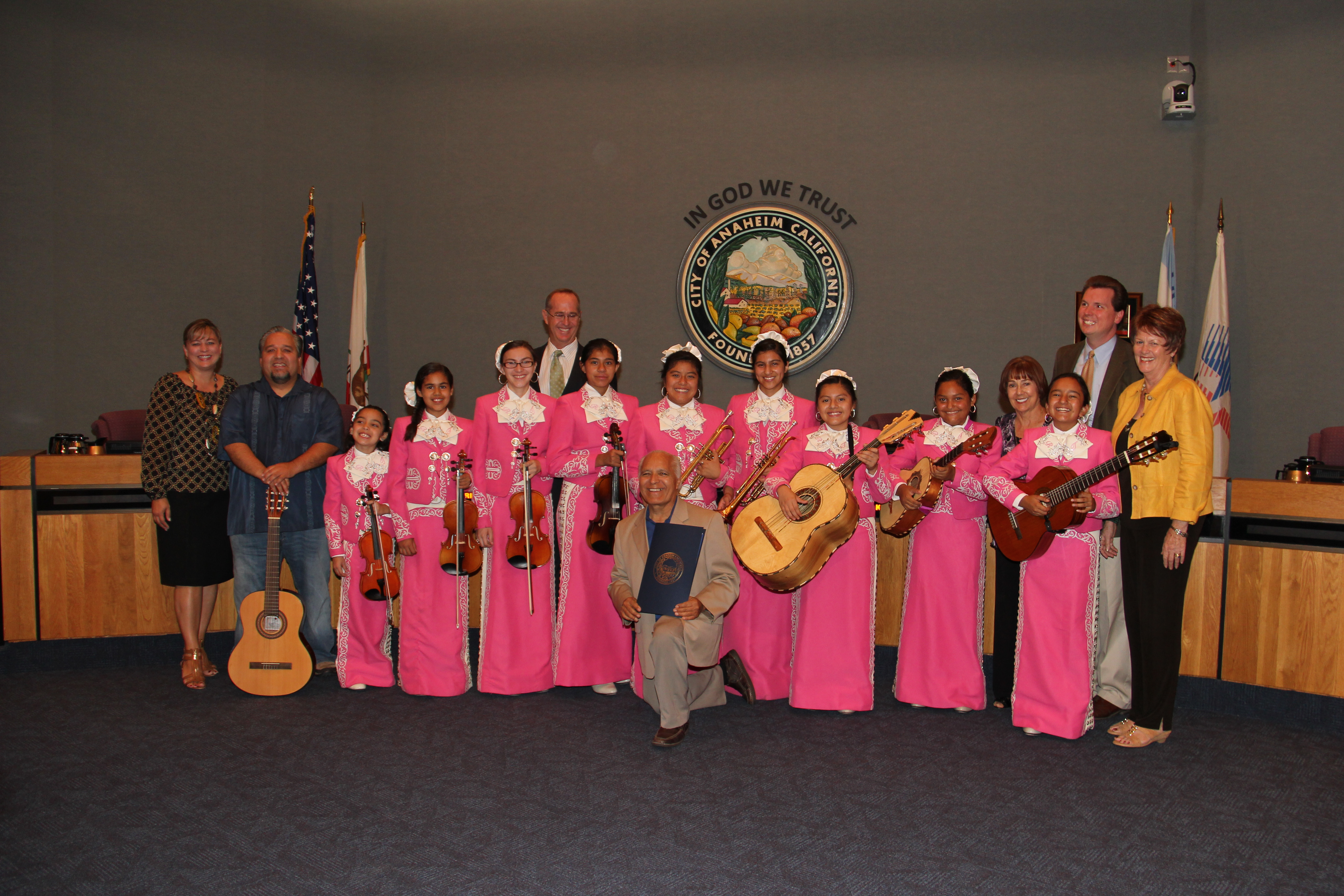 Band of women in pink dresses holding instruments with a man in the middle keeling down holding a blue folder