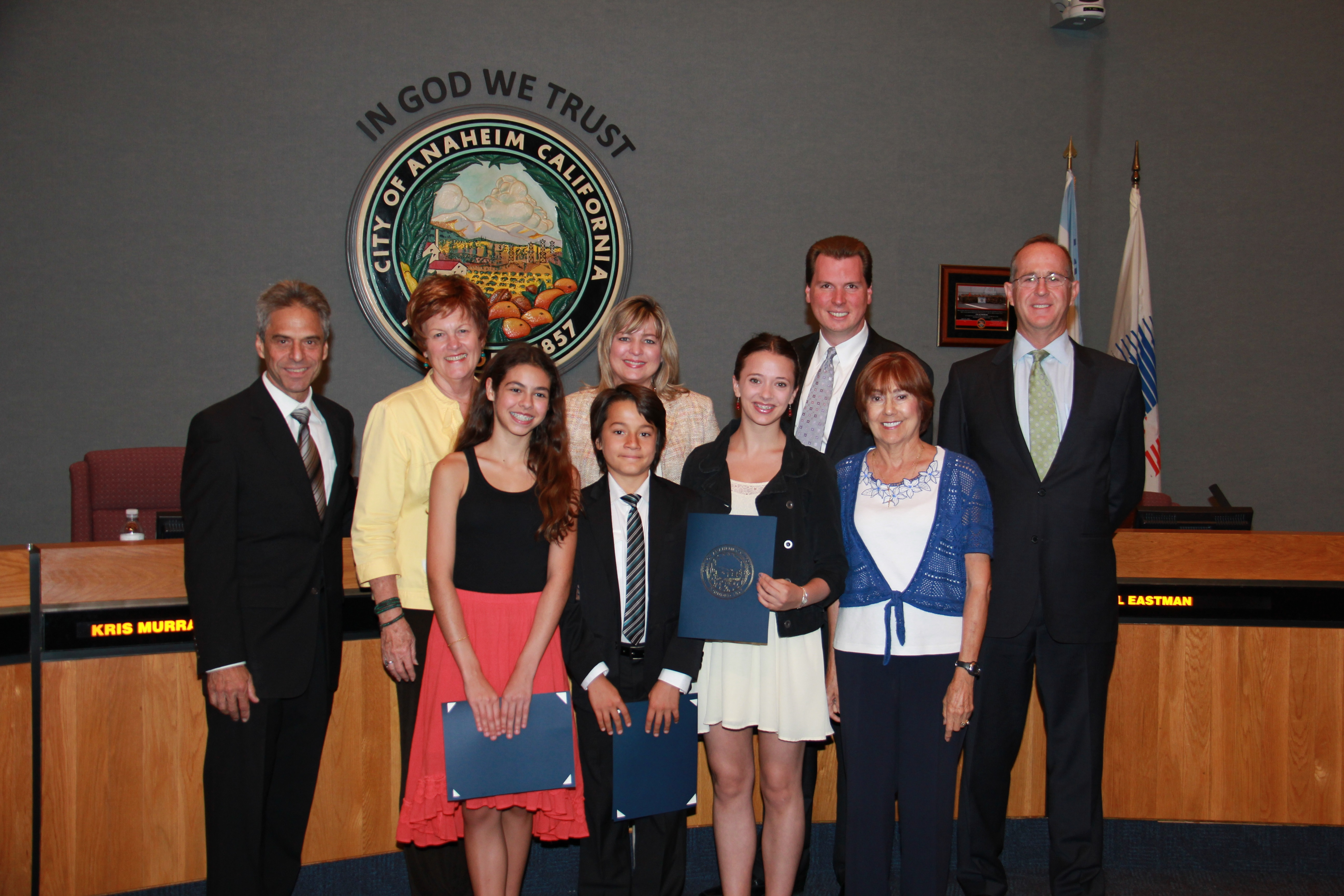 Two young girls and a young boy receiving awards from the City Council