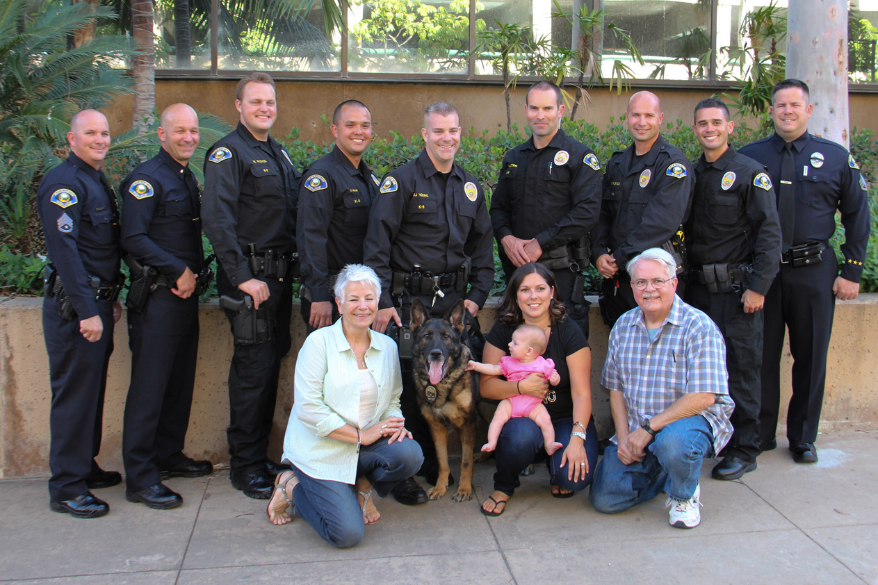 Out side taking a group photo with Police Officers, the police dog, and family members in front