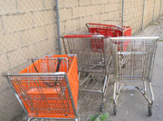 Four shopping carts 1 orange, 1 red, and 2 silver carts next to a brick wall