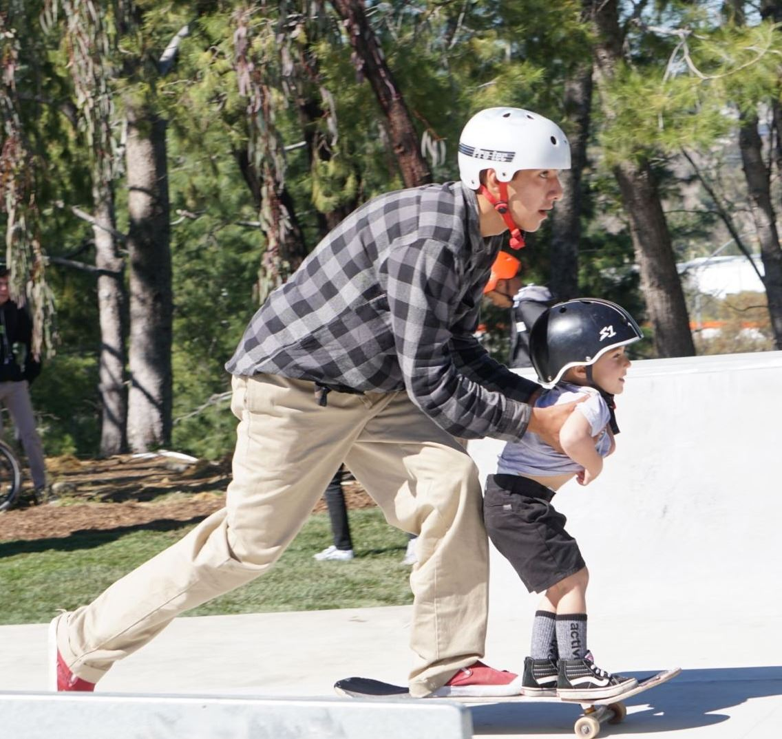 Adult and young boy skateboarding at Logan Wells Memorial Skate Park Opening