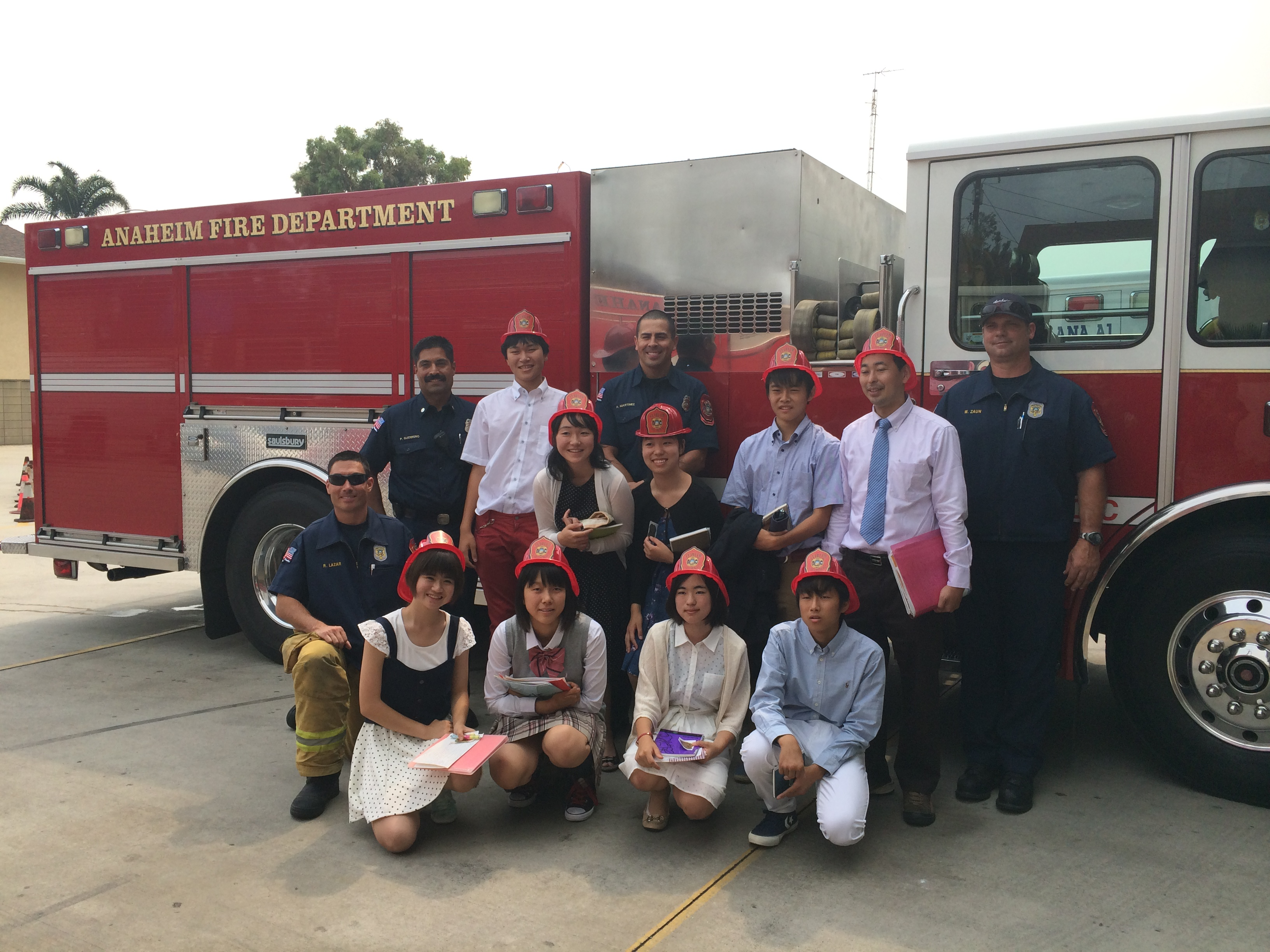 Students taking a group photo with the Anaheim Fire Department in front of their fire truck.