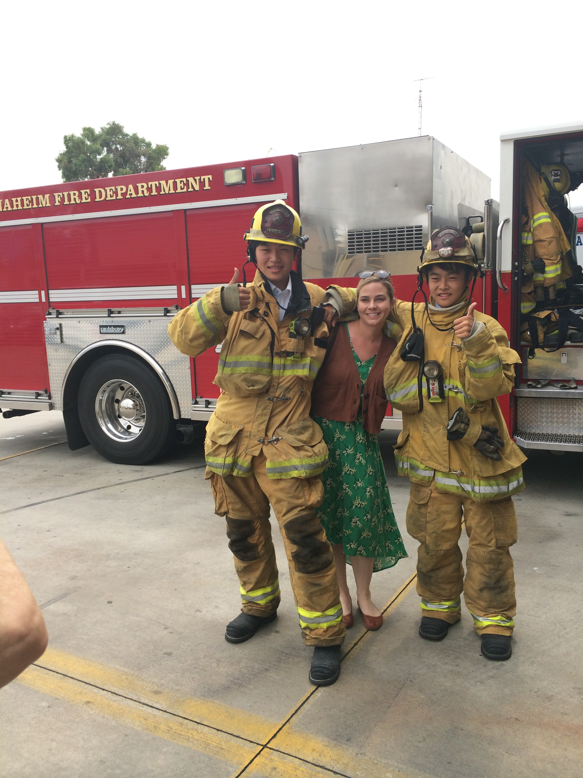Two students in firefighter jacket, pants, and helmet with a women in a green dress between them.