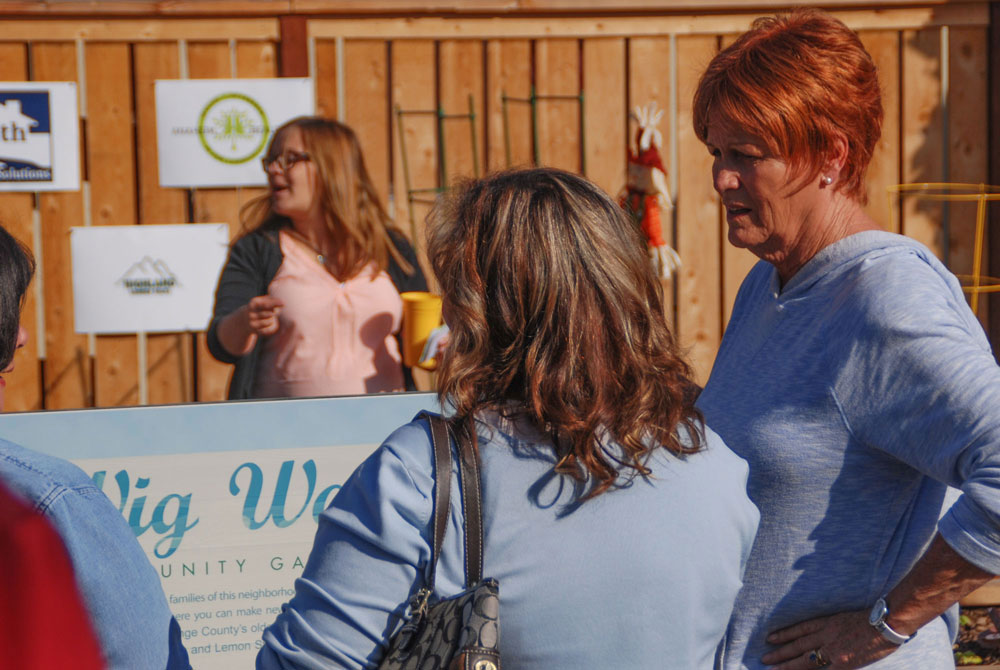 Two women talking in front of the Wig Wag sign
